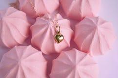 Un colgante de oro del corazón en fondo rosado de los merengues de la fresa Fotografía de archivo