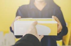 Un colis et une boîte aux lettres humains de participation de main pour la livraison et l'expédition images libres de droits