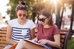 Un colpo all'aperto di due occhiali da sole femminili dei friendswears, vestito in maglietta casuale, ha letto il giornale intere Fotografia Stock Libera da Diritti