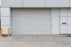 Un colpo del primo piano della porta automatica del rullo del metallo utilizzata in fabbrica, nello stoccaggio, in garage ed in m fotografie stock
