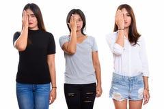 Un colpo dello studio di tre giovani amici asiatici della donna che sembrano sollecitati fotografia stock libera da diritti