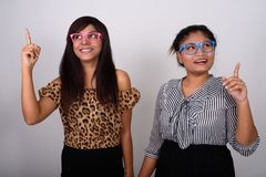 Un colpo dello studio di un whi sorridente di due giovani amici persiani felici della donna immagini stock