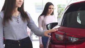 Un colpo potato di due donne che scelgono le automobili alla gestione commerciale immagine stock libera da diritti