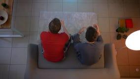 Un colpo superiore di due tifosi in indumenti da notte che si siedono sul sofà e sulla TV di sorveglianza nel salone video d archivio