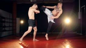 Un combatiente golpea abajo a su ayudante con un retroceso del salto almacen de metraje de vídeo