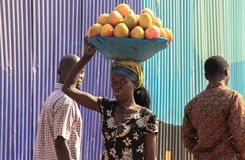 Un comerciante del mango lleva mercancías en su cabeza a través de las calles de Nairobi y hace caras imagen de archivo