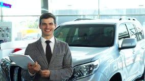 Un comprador feliz presenta un coche de la sala de exposición del automóvil almacen de video