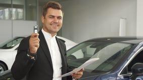 Un compratore soddisfatto legge i documenti dell'automobile fotografia stock libera da diritti