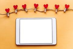 Un comprimé avec un écran blanc vide sur un fond jaune Prochaines pinces à linge avec le hachage en forme de coeur Photo libre de droits