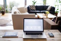 Un computer portatile, una compressa e un telefono con lo schermo domestico astuto fotografia stock libera da diritti