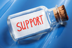 Un concept artistique d'un message dans une bouteille indiquant l'appui sur les vagues bleues Images libres de droits