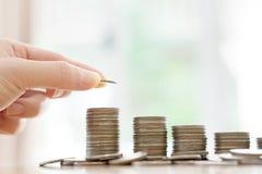 Un concept d'argent d'économie, main masculine mettant l'élevage de pile de pièce de monnaie d'argent Image libre de droits