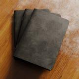 Un concetto del taccuino in bianco tre con copertina di carta strutturata nera sullo scrittorio di legno Modello orizzontale vuot Fotografia Stock