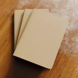 Un concetto del taccuino in bianco tre con la copertina di carta marrone del mestiere sullo scrittorio di legno Modello orizzonta Fotografia Stock