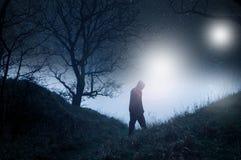 Un concetto della fantascienza di una figura incappucciata spettrale in un legno nell'inverno alla notte, profilato sulle stelle  fotografia stock libera da diritti