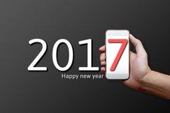 Un concetto di 2017 buoni anni, parte del corpo, fon del cellulare della tenuta della mano Immagine Stock Libera da Diritti