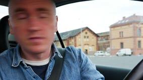 Un conducteur de jeune homme se déplace à l'envers Portrait en gros plan dans la voiture banque de vidéos