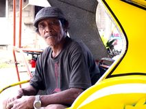 Un conducteur de tricycle se repose dans la cabine de son tricycle tout en attendant des passagers Photo libre de droits