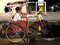 Un conducteur se repose dans son tricycle actionné par pédale, également connu localement As Photographie stock libre de droits