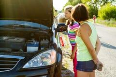 Un conductor de la mujer con un niño en una carretera nacional, cerca de un coche quebrado Fotografía de archivo libre de regalías