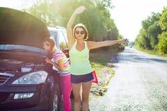 Un conductor de la mujer con un niño en una carretera nacional, cerca de un coche quebrado Fotografía de archivo