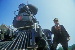 Un conductor del motor de vapor comprueba el tiempo como él se coloca cerca del cowcatcher en el frente, Eureka Springs, Arkansas Imagen de archivo libre de regalías