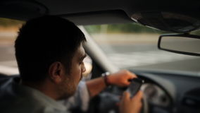 Un conductor masculino que manda un SMS en un teléfono móvil mientras que conduce almacen de video