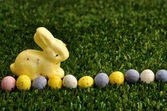 Un conejito amarillo con una fila de los huevos de Pascua manchados Imagen de archivo