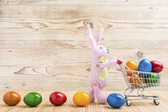 Un conejito de pascua con el carro de la compra y los huevos coloridos Fotos de archivo