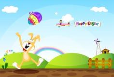 Un conejito de pascua que lanza los huevos de Pascua alrededor en un h Foto de archivo libre de regalías
