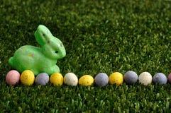 Un conejito verde con una fila de los huevos de Pascua manchados Imagen de archivo libre de regalías