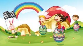 Un conejito y niños con los huevos de Pascua Foto de archivo libre de regalías