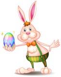 Un conejo que sostiene un huevo de Pascua stock de ilustración