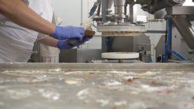 Un confettiere fa il dolce del biscotto con crema, spande la crema con latte condensato sui dolci con l'aiuto di moderno archivi video