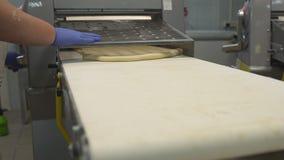 Un confettiere femminile srotola la pasta su uno sheeter per produrre le torte ed i panini Fabbricazione del forno, industria ali stock footage
