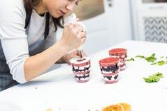 Un confitero prepara una bagatela en tres tazas Los postres est?n en la tabla blanca en la cocina El concepto de hecho en casa foto de archivo libre de regalías