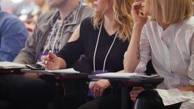 Un congreso de negocios en el pasillo Gente que se sienta por las tablas y que hace marcas en el cuaderno metrajes