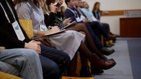 Un congreso de negocios en el pasillo Gente que sienta y que hace marcas en el cuaderno metrajes