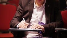Un congreso de negocios en el pasillo Un hombre que se sienta por la tabla y que hace marcas en el cuaderno almacen de video