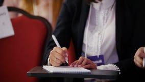 Un congreso de negocios en el pasillo Una mujer que se sienta por la tabla y que hace marcas en el cuaderno metrajes