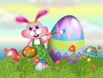 Un coniglietto che dipinge l'uovo nel giardino Fotografia Stock Libera da Diritti