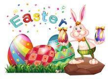 Un coniglietto sopra la roccia con le uova di Pasqua Fotografia Stock