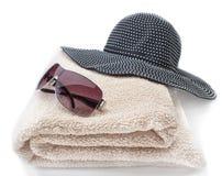 Un conjunto de vidrios, de una toalla y de una Panamá para la playa el vacaciones Fotos de archivo