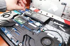 Un connaisseur nettoie un refroidisseur d'ordinateur portable Système de refroidissement souillé d'ordinateur photographie stock