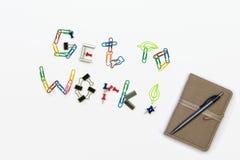 ¡Un conseguir de trabajar! texto hecho de clips y de pernos, y un cuaderno con una pluma en un fondo brillante Fotografía de archivo