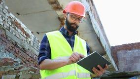 Un constructeur d'ingénieur dans un comprimé d'utilisation de casque, un plan de construction de démolition et regarder le projet clips vidéos