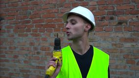 Un constructor con un taladro metrajes