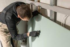 Un constructor de trabajo del hombre hace una marca en la mampostería seca para el cableado eléctrico Construcción de la mamposte imagen de archivo libre de regalías