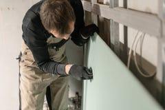 Un constructor de trabajo del hombre hace una marca en la mampostería seca para el cableado eléctrico Construcción de la mamposte fotografía de archivo libre de regalías