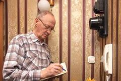 Un contador eléctrico del hombre mayor Imágenes de archivo libres de regalías